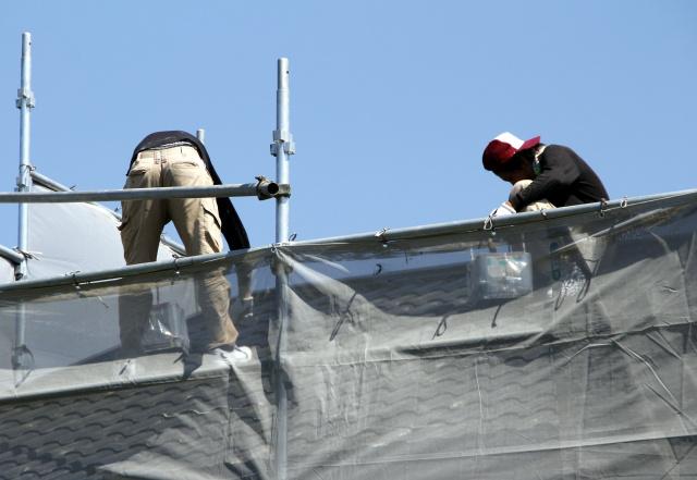 屋根塗装をしている人